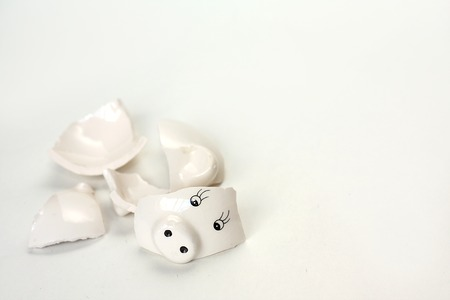 a small broken and emptied white piggy bank is isolated on a plain white background, with room for copy space.