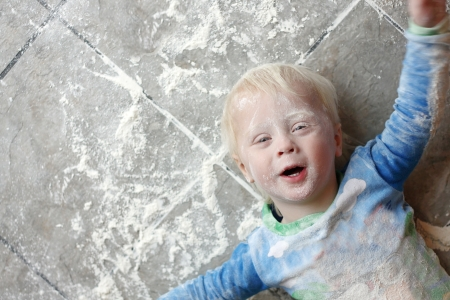 a one year old small child is laying on a very messy kitchen floor, covered in white baking flour   Room for text, copy space Stockfoto
