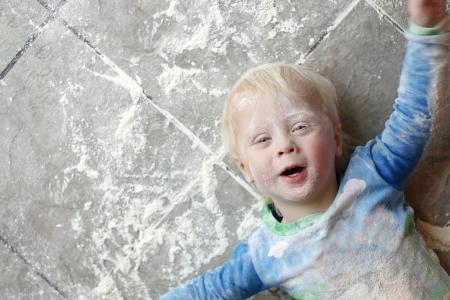 Een jaar oud klein kind is tot op een zeer rommelige keuken vloer, bedekt met witte bakmeel Kamer voor tekst, kopieer ruimte Stockfoto - 23955736