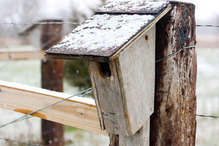 a wooden, handmade birdhouse is hanging on a wood railroad tie fence post in the country in the winter snow  photo