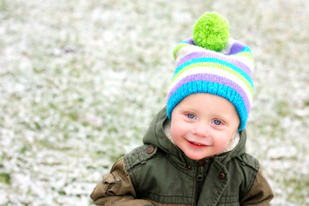 stocking cap: Close up portrait of a happy and smiling one year old baby boy in a stocking hat, outside in freshly fallen snow on a winter day   Room for text, copyspace