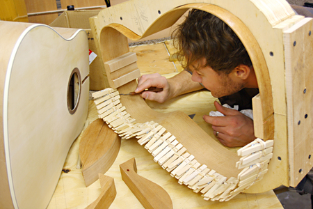 whittle: a young man who is a luthier is making hand made guitar out of wood in his home workshop  Stock Photo