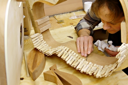 a young man who is a luthier is making hand made guitar out of wood in his home workshop  Reklamní fotografie