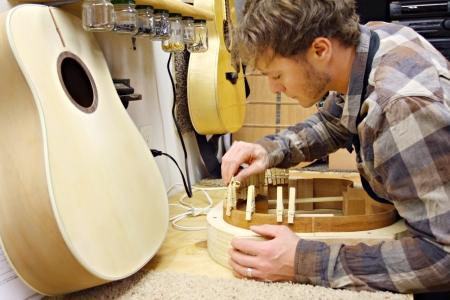 기타 제작자 인 젊은 남자가 자신의 집 작업장에서 나무로 손으로 만든 기타를 만드는