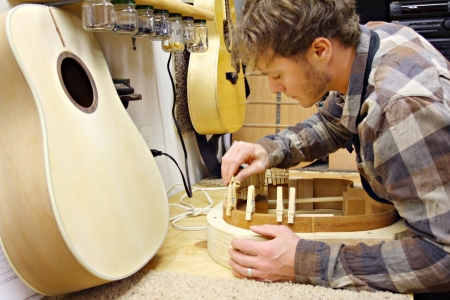 a young man who is a luthier is making hand made guitar out of wood in his home workshop  Banque d'images