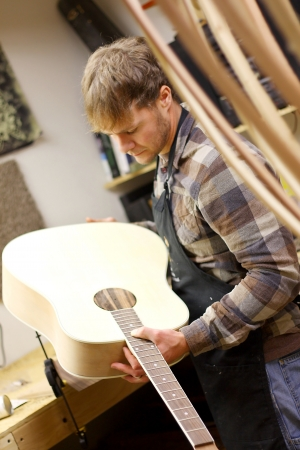 A young man who is a luthier is in his workshop inspecting an acoustic guitar that he is building