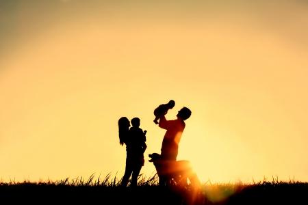 4 人、母、父、赤ちゃんと子、およびコピーの領域またはテキストのための部屋との sunsetting 空の前に彼らの犬の幸せな家族のシルエット