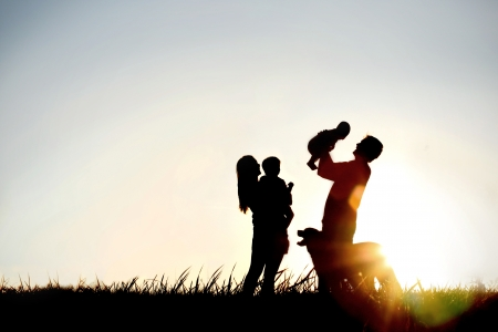 A silhouette of a happy family of four people, mother, father, baby, and child, and their dog in front of a sunsetting sky, with room four copy space or text Stockfoto