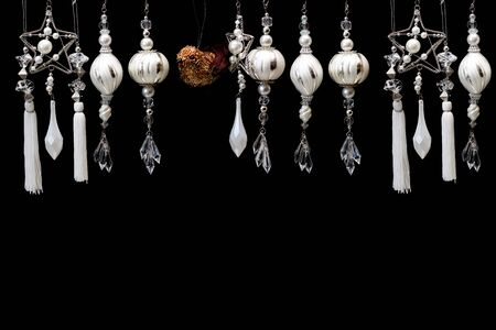 tassles: a row of silver, gold,  and white dangling christmas tree ornaments are hanging in front of a black  Stock Photo