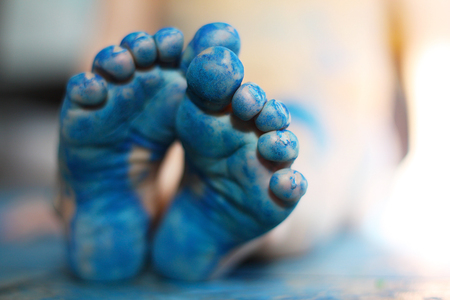 painted toes: a close up on the bottom of the feet of a small child, that have been painted blue.  Very shallow depth of field with focus on toes of front foot.