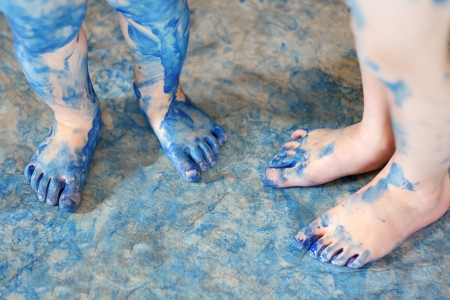two pairs of very messy blue painted kids feet are standing on a floor covered in paint