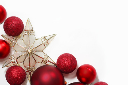 Red sparkly Christmas Bulb Decorations and a gold tree topper star are in the corner framing a white for text, copyspace photo