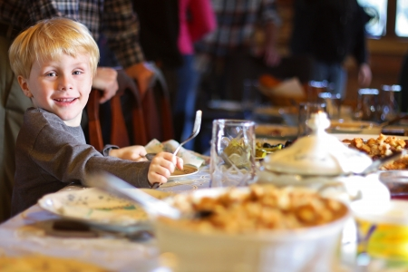 little table: a happy young child is smiling as he sits at the holiday dinner table with a fork and plate, waiting for his meal