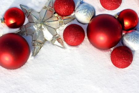 freshly fallen snow: una collezione di rosso, argento e oro decorazioni natalizie e bulbi stanno gettando fuori che incornicia la neve appena caduta per il testo, copyspace.