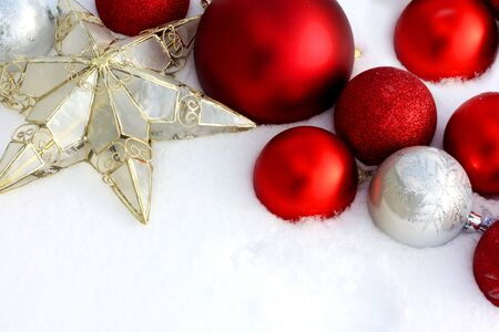 christmas bulbs: Red and Silver Christmas Ornament Bulbs and a star are framing the top corner of white, freshly fallen snow background, with room for text, copyspace