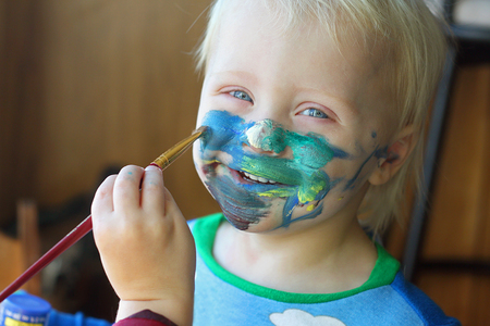 sneaky: a one year old baby boy is smiling as his big brother is painting all over his face with blue and green colors. Stock Photo