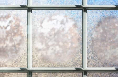 background of a a window in the winter, frosted over with ice, with hints of blue on white.  Room for text, copyspace.