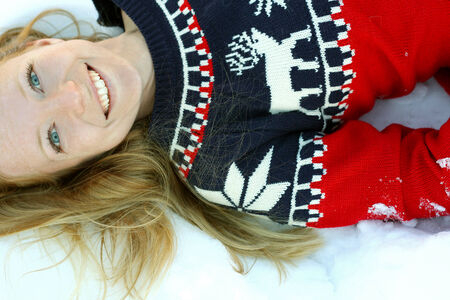 woman sweater: a 30 year old, attractive, smiling woman wearing a Christmas ski sweater, is lying in the winter snow outside