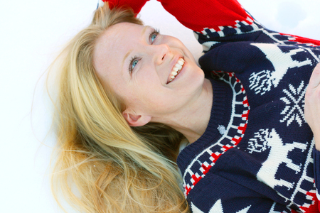 30 year old: a 30 year old, attractive, smiling woman wearing a Christmas ski sweater, is lying in the winter snow outside