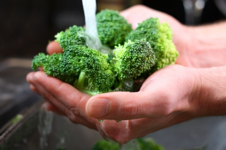The hands of a man are holding fresh broccoli sprouts under running water, and washing them in the kitchen sink  Imagens