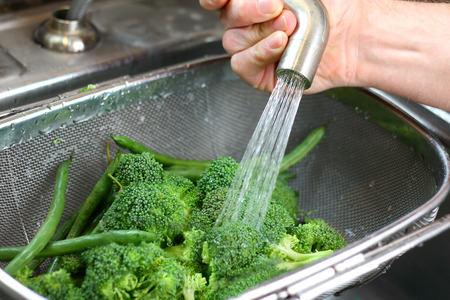 The hand of a man is washing fresh broccoli and green bean vegetables in a strainer in the kitchen sink 免版税图像