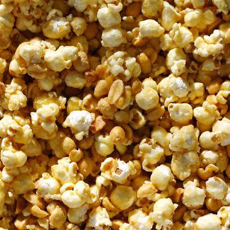 popcorn bowls: a square background of sweet candy caramel glazed popcorn with peanuts, leaves room for text, copyspace