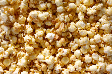bowl of popcorn: a background of sweet candy caramel glazed popcorn with peanuts, leaves room for text, copyspace