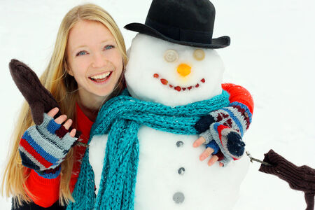 tophat: a happy young woman is standing outside in the winter snow, hugging a snowman that she just built.