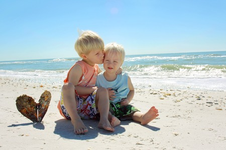 a young child is hugging and kissing his baby brother as they sit on the white sand beach by the ocean