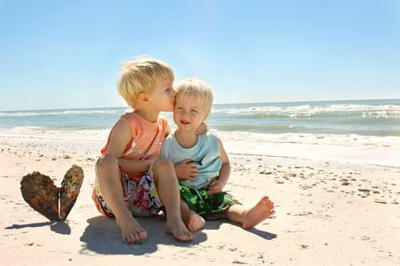 two children, a young child and his baby brother, are sitting on the beach next to the ocean shore, hugging and kissing eachother