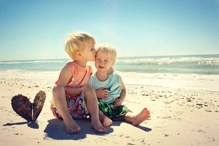big and small: two children, a young child and his baby brother, are sitting on the beach next to the ocean shore, hugging and kissing eachother  Vintage Style Color