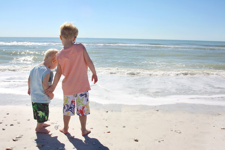 a young child is holdiong the hand of his baby brother as they look at the ocean while standing on the beach