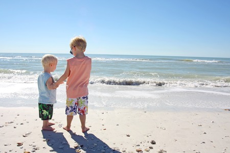 a young child is standing smiling on the beach on the ocean shore, holding his baby brothers hgand as they look at the water