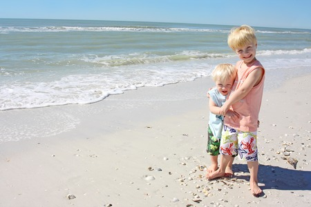 a young child is standing smiling on the beach on the ocean shore, hugging his baby brother in his arms Stock Photo