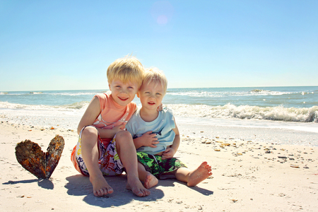 eachother: a young child and his baby brother are sitting on the beach in front of the ocean, hugging eachother and sitting by a heart shaped sea shell. Stock Photo