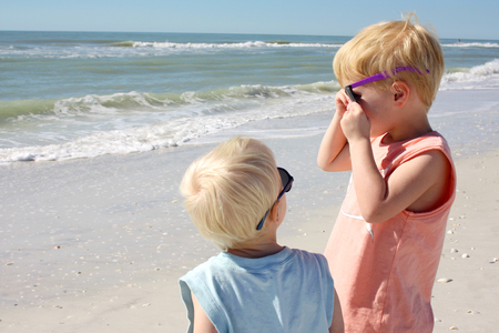 a young child is looking up at his older brother as he puts on sunglasses on the beach by the ocean Stock Photo