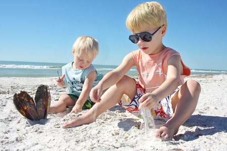 a young child and his baby brother are playing in the sand at the beach, by the ocean shore photo