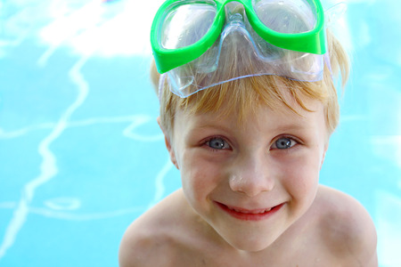 a little child is smiling as he stands by the swimming pool with goggles on his head