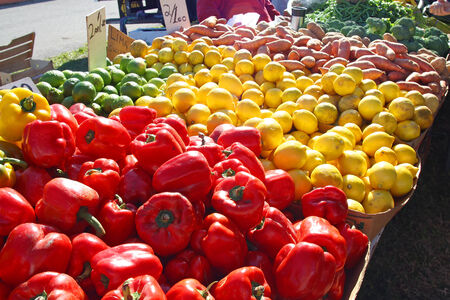 Pile of Bright Red and Yellow Bell Peppers, lemons, limes, and various other fruits and Vegetables on sale table at at Farmers Market photo
