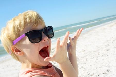 a young child is smiling and looking excited as he stands on the beach by the ocean