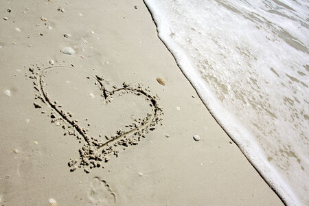 seashell: a heart is drawn in the sand next to the ocean shore