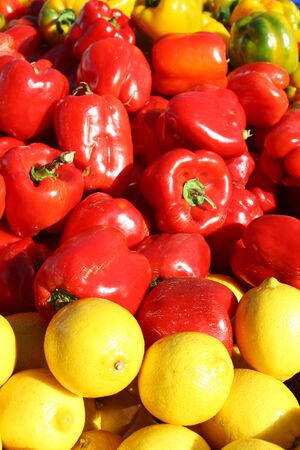 a pile of bright red peppers and yellow lemons outside for sale at farmer photo