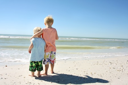 arms around: two young children, a boy and his baby brother are standing on the beach shore with their arms around eachother, looking at the ocean Stock Photo