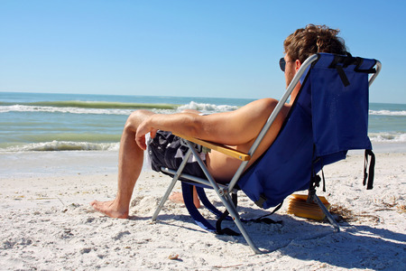 a young caucasian man is lounging in a beach chair and sunbathing by the ocean Banco de Imagens