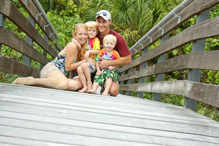 a young, happy family of four people including mother, father, baby and child are sitting on a wooden bridge in front of a tropical forest photo