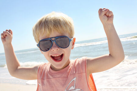 boy muscles: a happy young child is holding up his fists and flexing his muscles on the beach in front of the ocean