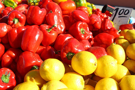 a pile of red peppers and yellow lemons outside for sale at farmer photo