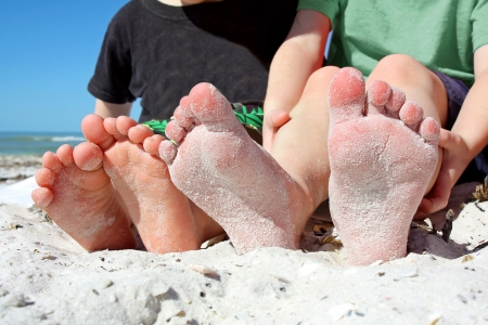 two young children's feet are seen, covered in sand as they sit on the beach by the ocean