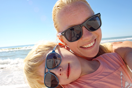 a young mother and her son are smiling as they pose for a self portrait on the beach by the ocean