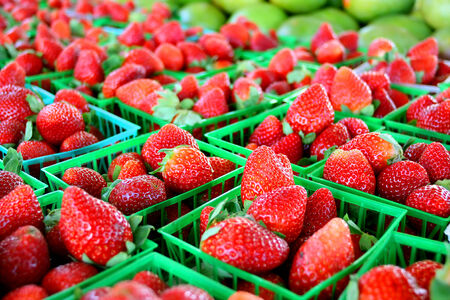 a collection of fresh strawberries are gathered in baskets on a sale table at a farmer's market. photo